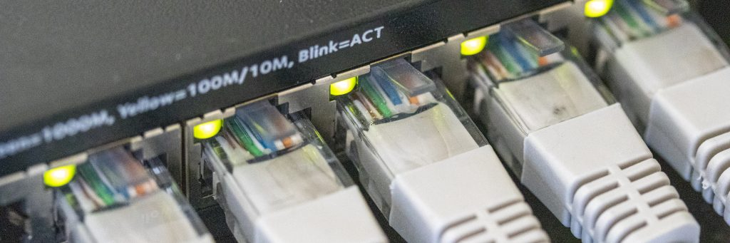 A photo of Cat5e Ethernet cables plugged into a switch, link lights on the ethernet ports are illuminated.